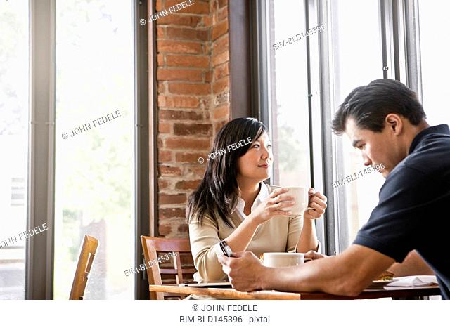 Chinese couple drinking coffee in cafe