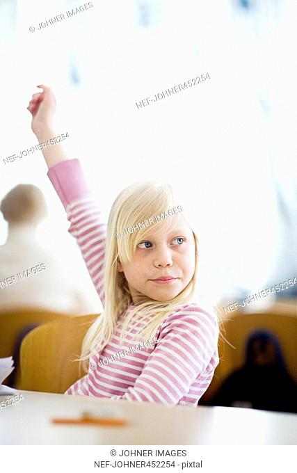A girl reaching up her hand in a classroom, Sweden