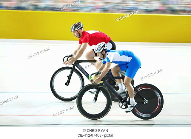 Track cyclists racing in velodrome