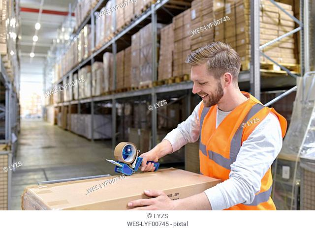 Smiling man in factory hall wearing safety vest closing cardboard boax