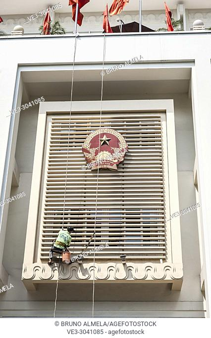 Worker cleaning the facade of governmental building in Hanoi, Vietnam