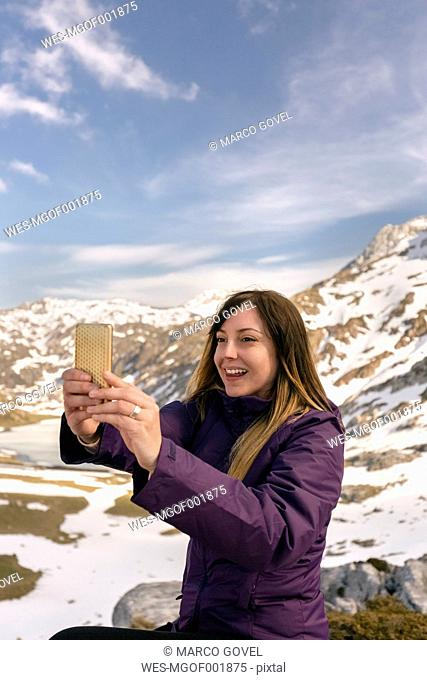 Spain, Asturias, Somiedo, smiling woman taking a selfie in mountains