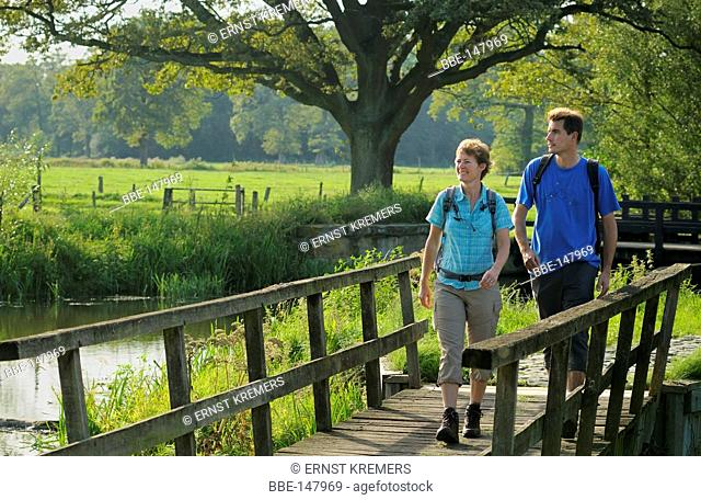 A couple walks over a wooden brigde during their hike