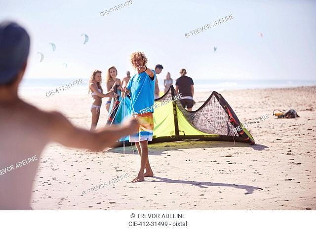 Friends preparing kiteboarding kite on sunny beach