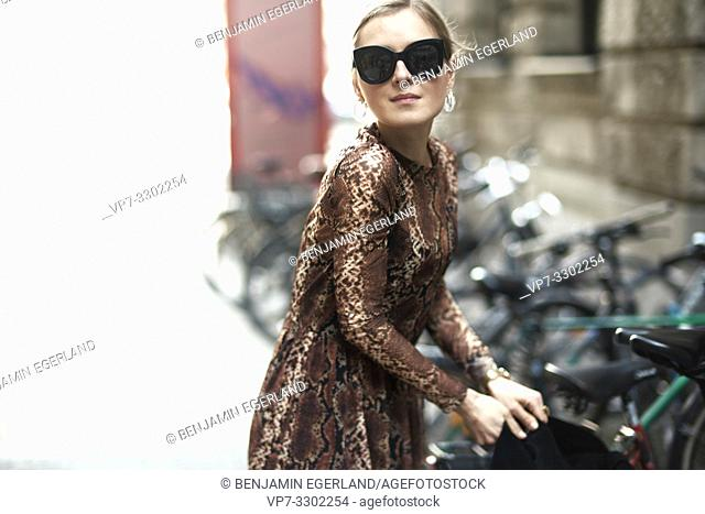 fashionable woman next to parked bicycles in city, in Munich, Germany