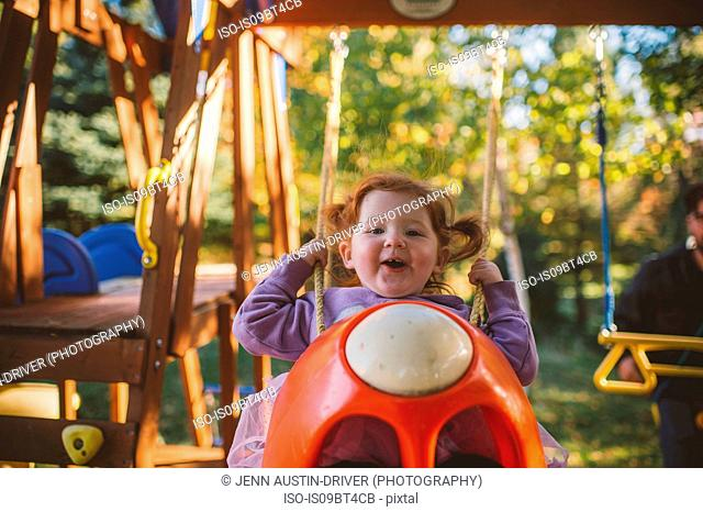 Girl with red hair swinging on playground swing, portrait