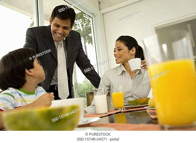 Close-up of a young woman having breakfast with her son and a mature man standing beside them