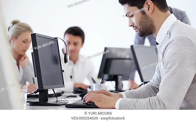 Handsome office worker working busily on his computer with colleagues in the background