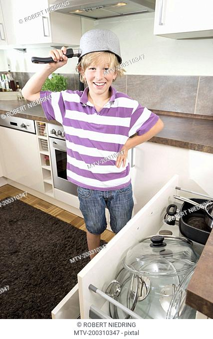 Happy boy with pan on his head in kitchen, Bavaria, Germany