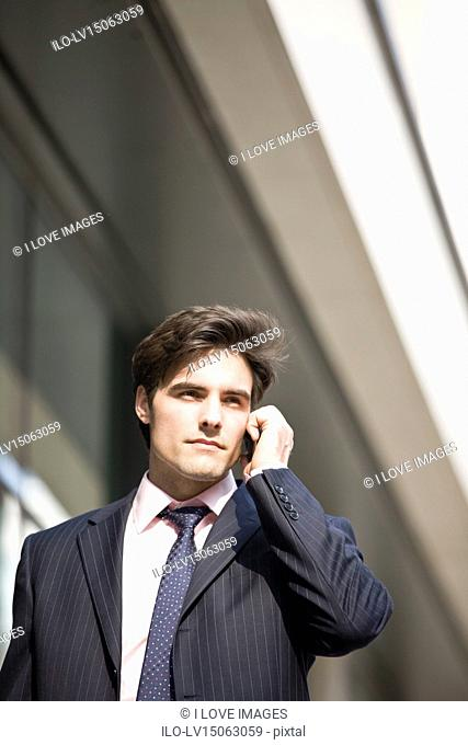 A businessman walking along the street, talking on a mobile phone