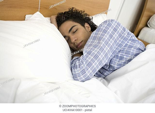 Young hispanic man lying in bed sleeping