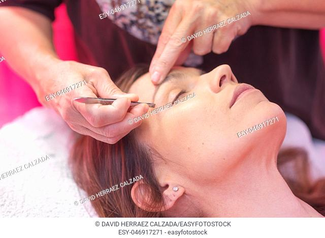 Young woman havind professional eyebrow correction at spa salon