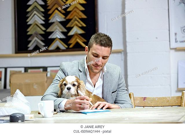 Mid adult man with dog at making notes at desk in picture framers workshop