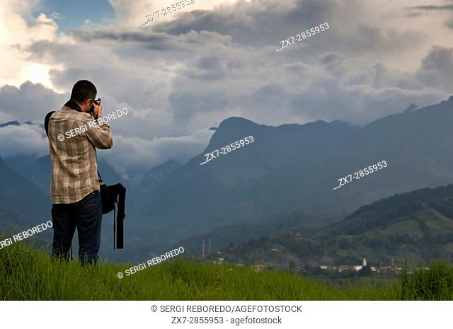 A tourist take photos of the mountainous landscape of the National Park of Los Nevados, Colombia. The Los Nevados National Natural Park is located in the...
