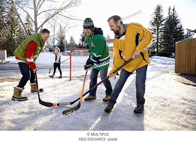 Men playing ice hockey in snowy driveway