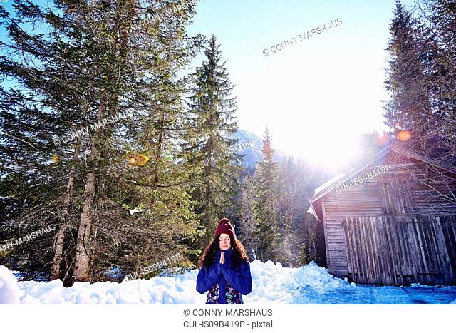 Woman practicing yoga, meditating in snowy sunlit forest, Austria