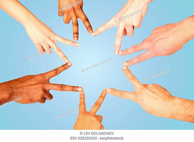 diversity, race, ethnicity, international and people concept - group of hands showing peace hand sign over blue background