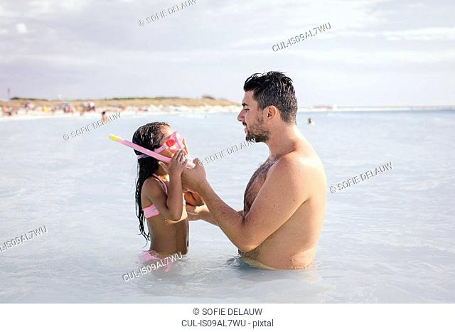 Father teaching daughter how to snorkel in sea, Tuscany, Italy