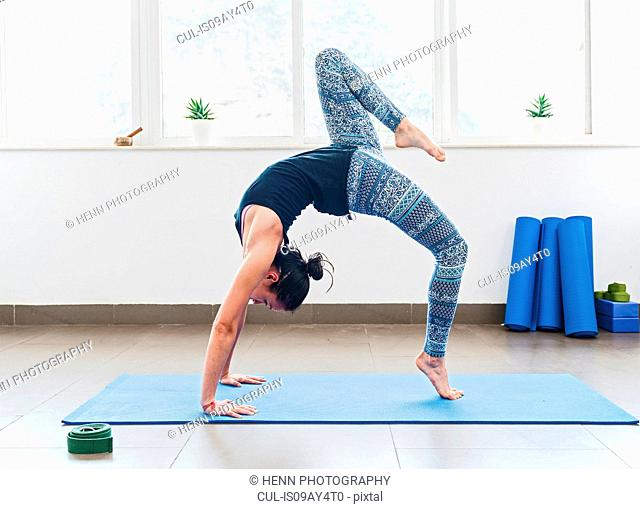Woman practising yoga in room
