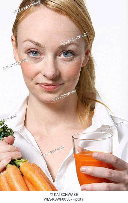 Young woman holding bunch of carrots, smiling, portrait