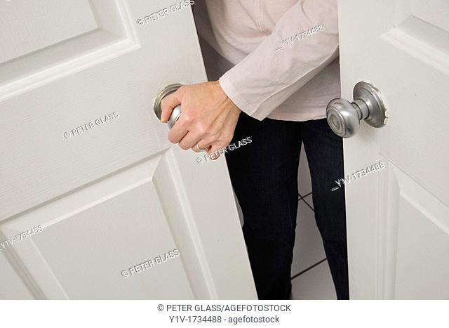 Middle-age woman's hand on a door handle
