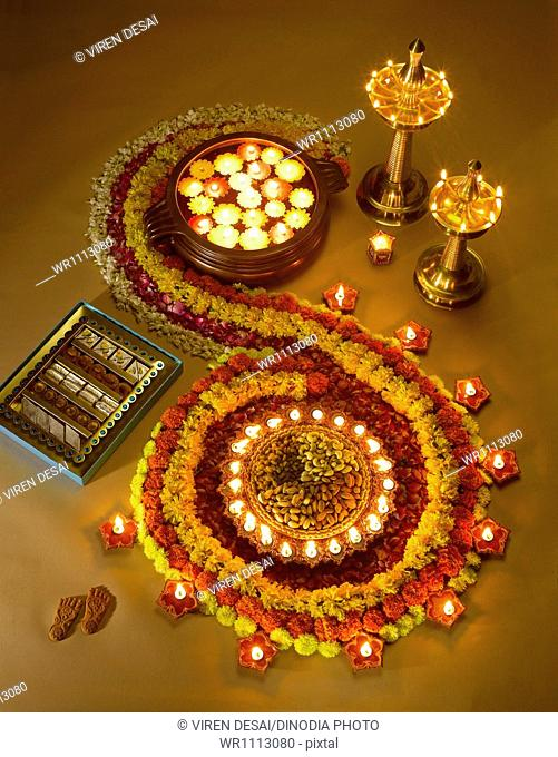 Diyas oil lamps sweets and flowers arrangement for diwali festival ; India