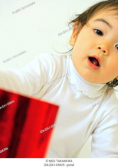 Portrait of a baby girl holding a paper bag