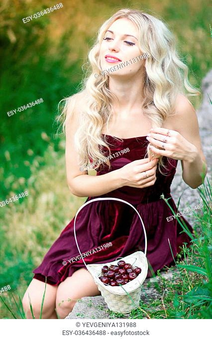 Portrait of beautiful young woman with berries in basket