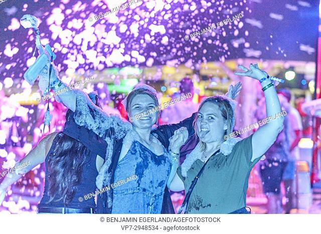 happy friends enjoying summer foam party at music festival. North American ethnicity. In holiday destination Hersonissos, Crete, Greece