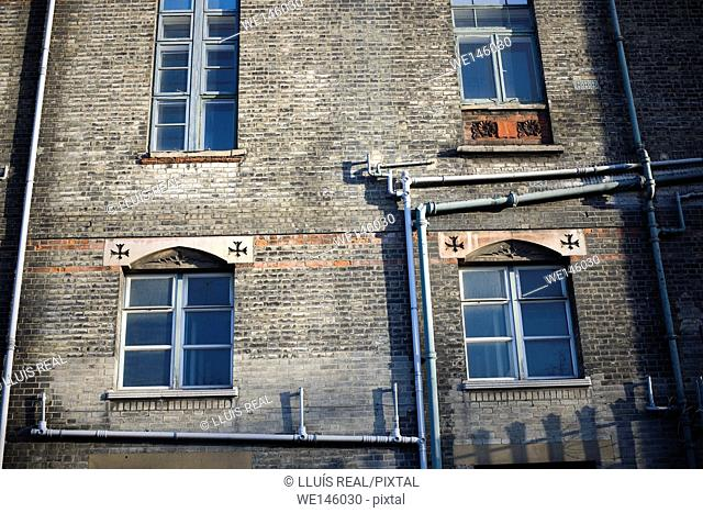 facade of a brick building with windows and drain pipes. England, UK, Europe