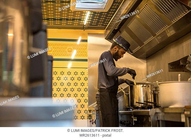 Man with hat cooking in commercial kitchen of food truck