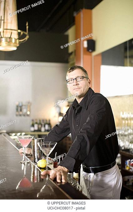 Male bartender leaning on bar