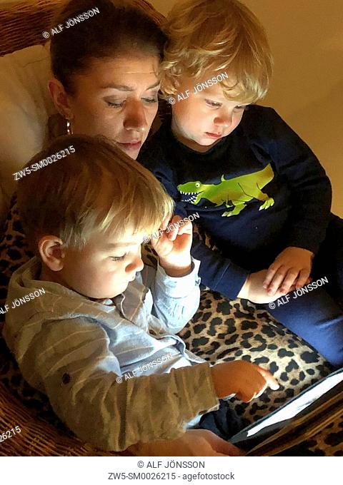 Woman read a tablet computer with two boys, 3 years old, in Scania, Sweden