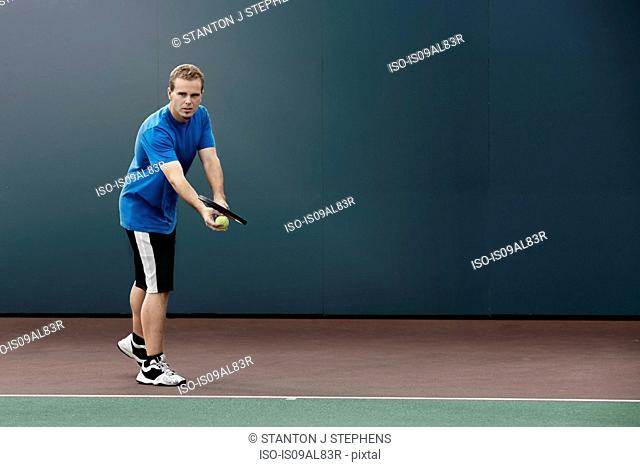 Tennis player about to serve ball in tennis court