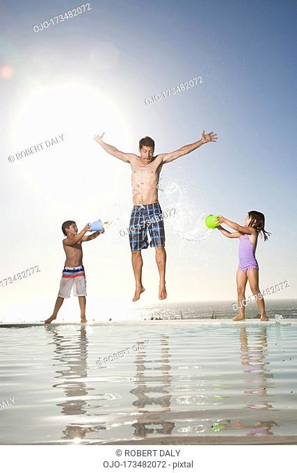 Children splashing water on man