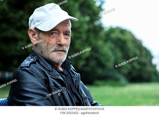 Karl Marx Allee, East-Berlin, Berlin, Germany. Portrait of a senior adult man, spending his evening near a plantation in his neighborhood