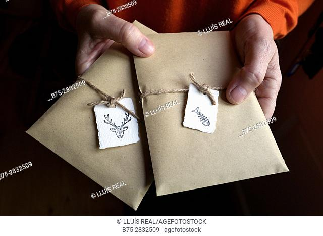 Woman's hands holding two gift packages, tied with a string and labelled with animal images