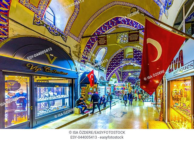 Unidentified Tourists visiting and shopping in the Grand Bazaar in Istanbul. Interior of the Grand Bazaar with Turkish Flag on the foreground