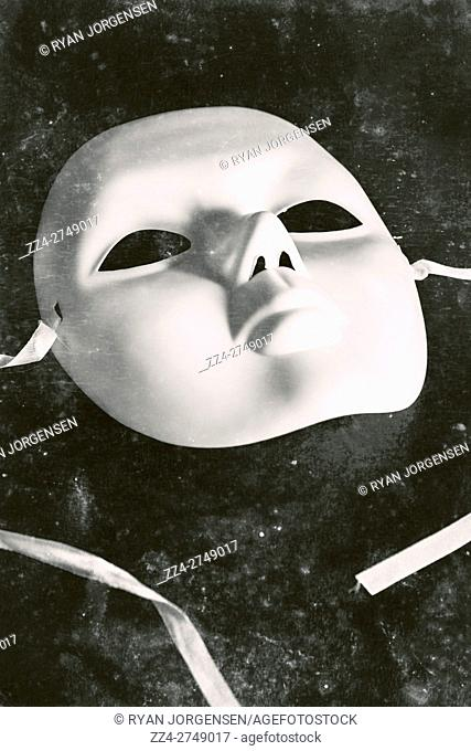Vintage performing arts still life on a textured mime mask with faded scratches and scuff marks. Stage of old