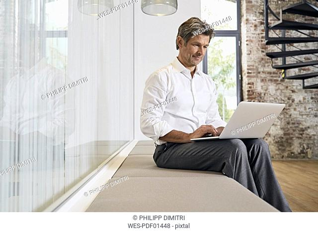 Businessman sitting on bench in modern office using laptop