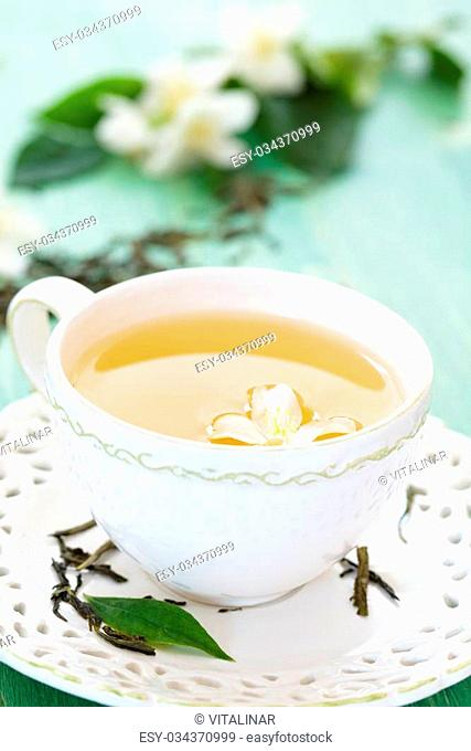 Cup of green tea with flowers of jasmine