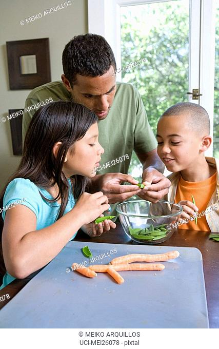 Father and children shelling peas