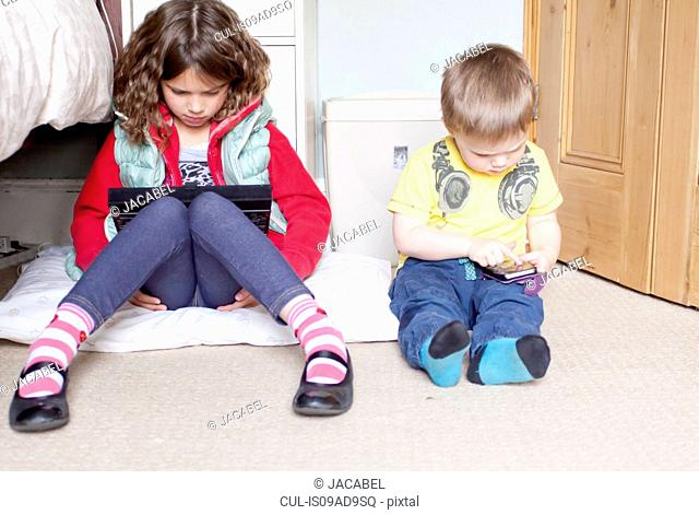 Children using digital tablet and cellular phone