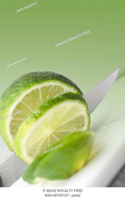 A knife cutting a lime