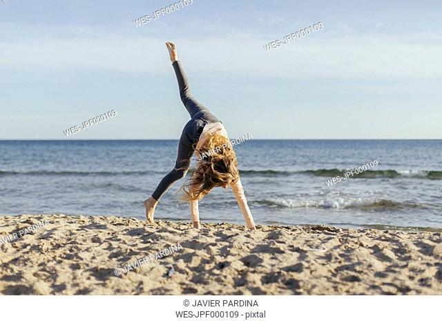 Spain, Lleida, woman on the beach, turning wheel