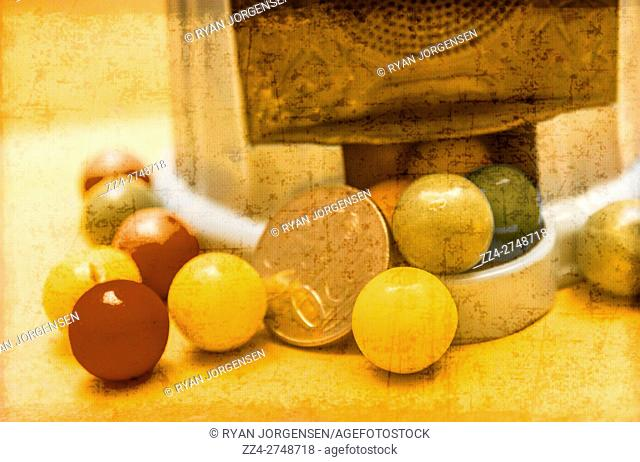 Close up view on various colored marbles or gumballs and coin in dispenser with worn surface print effect