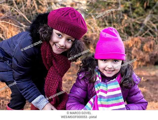 Portrait of two smiling little girls in a park on a winter day