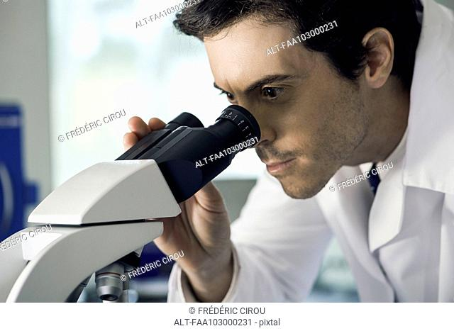Doctor analyzing lab results under microscope
