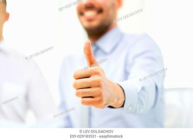 business, people, success and gesture concept - hand of smiling businessman showing thumbs up at office
