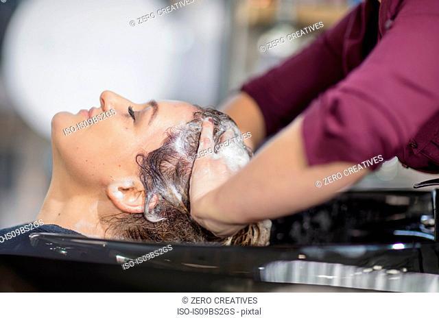 Hairdresser shampooing customer's hair in salon